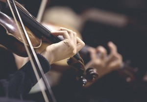 The girl's hand on the strings of a violin in dark colors