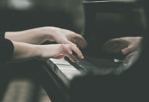 Hands girl playing piano closeup